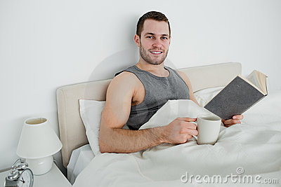 Young man reading a novel while drinking a coffee