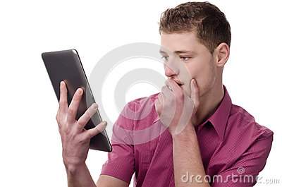 Young man reading a shocking news on the tablet.