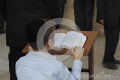 Young man reading from the Toran during Shabbat in Jerusalem Editorial Photography