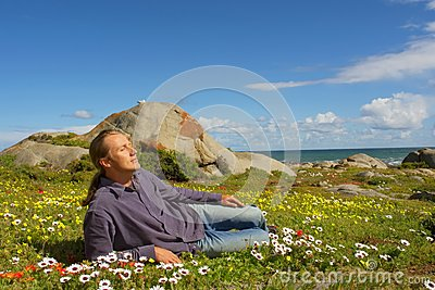 Young man relaxes lying on flower field