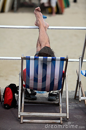 Young Man Relaxing in Deckchair on Beach