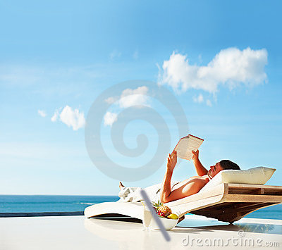 Young man relaxing on his holiday, reading a book