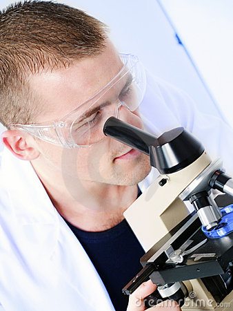 Young man researching on a microscope