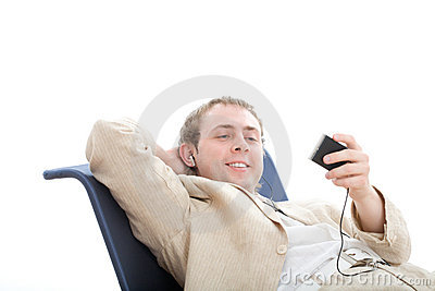 Young man rest in chair and listens digital player