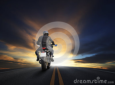 Young man riding big bike motocycle on asphalt high way against