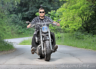 Young man riding a chopper on a road
