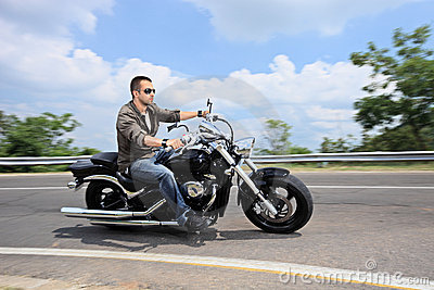 Young man riding a motorcycle on an open road