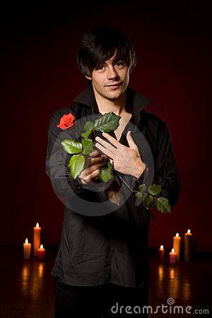 Young  man with rose in black shirt on red