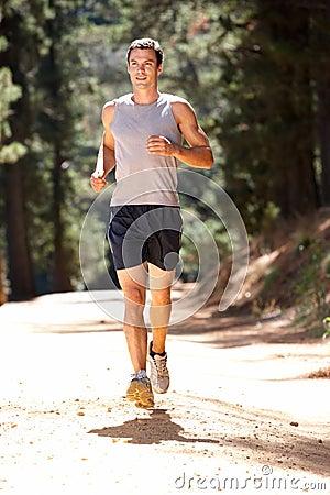 Young man running along country lane