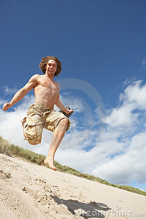 Young Man Running Down Sand Dune