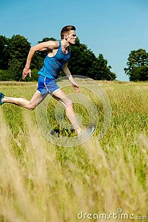Young man running through meadows