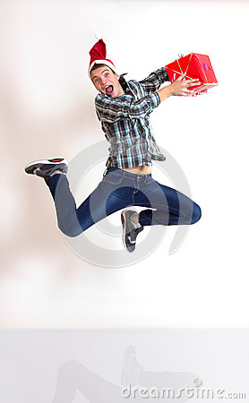 Young man in santa cap jumping with gifts
