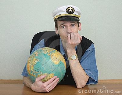 Young man in a sea cap of captain with globe