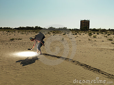 Young man searching through sand with light