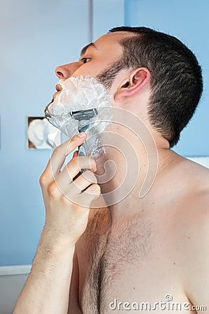 Young man shaving his beard
