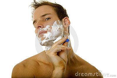Young man shaving his beard