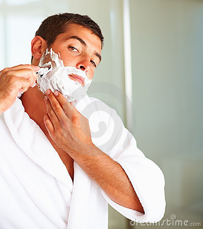 A young man shaving his beard