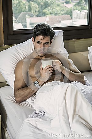Free Young Man Shirtless On His Bed With A Coffee Or Tea Cup Stock Photo - 108747210