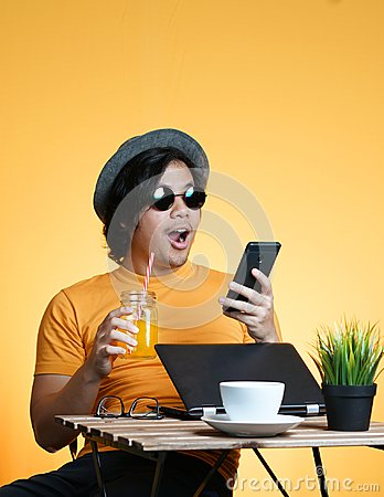 Free Young Man Shocked And Excited Holding Smartphone While Working O Stock Photos - 117944833