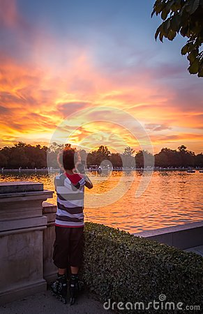Young man shooting the sunset in Buen Retiro park Editorial Image