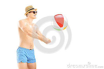 Young man in shorts playing with a beach ball