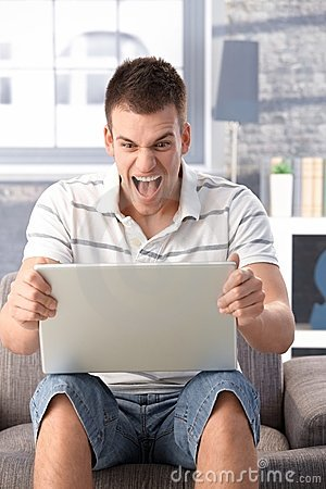 Young man shouting at laptop screen