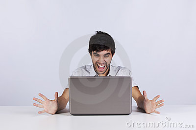 Young man shouting to a laptop