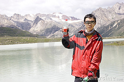 Young man show water bottle in nature
