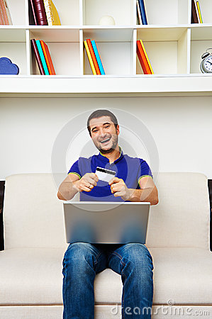 Young man showing credit card and smiling