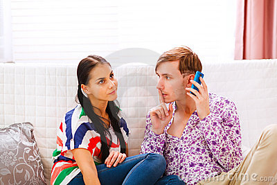 Young man showing shh... gesture to girlfriend