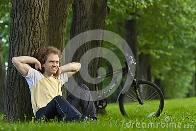 Young man siting under the tree near his bycicle