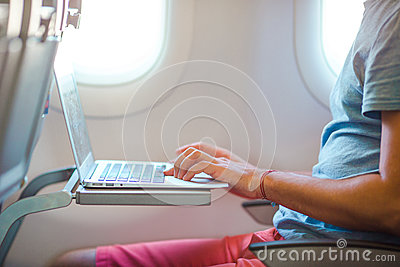 Young man sitting in the airplane and working on his laptop Stock Photo