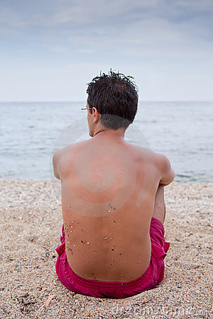 Young man sitting alone on the beach