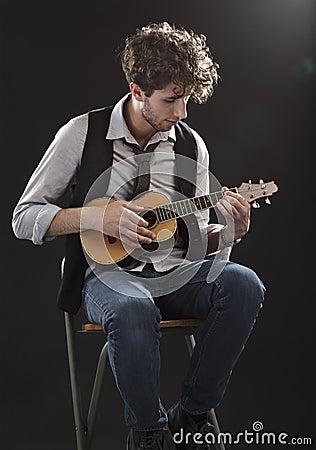 Free Young Man Sitting And Playing A Ukulele Royalty Free Stock Photo - 24630165