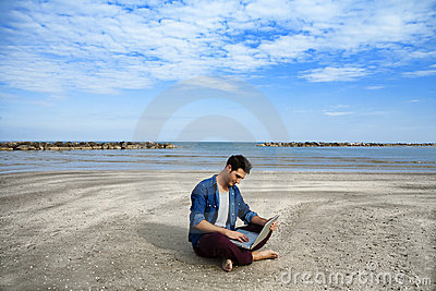 Young man sitting on beach with laptop