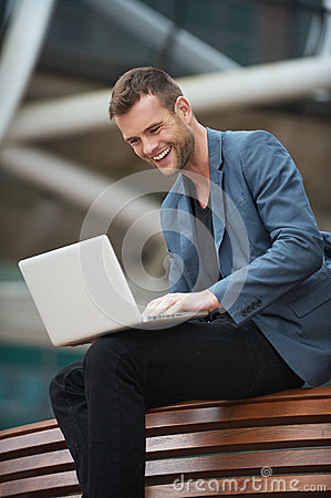Young Man Sitting in Bench with his Laptop