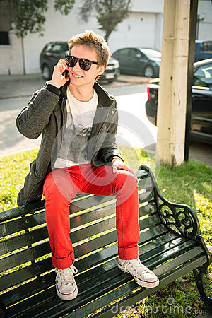 Young man sitting on a bench talking on the phone