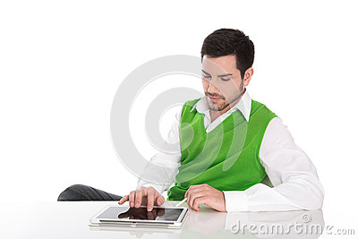 Young man sitting at desk with his tablet computer.
