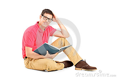 Young man sitting on floor and reading a book
