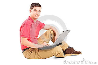 Young man sitting on the floor and working on a laptop