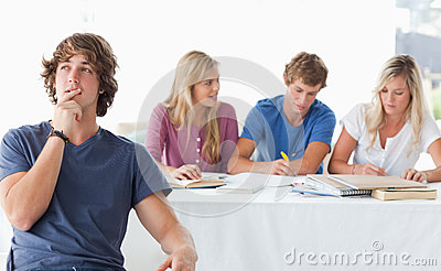 A young man sitting in front of his working class mates and thinking