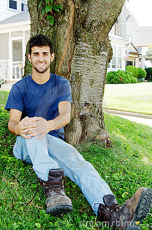 Young man sitting in front yard