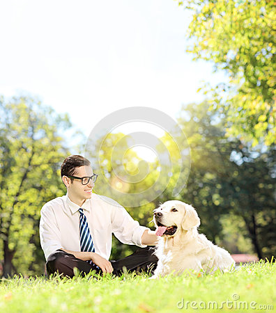 Young man sitting on grass next to a dog in a park on a sunny da