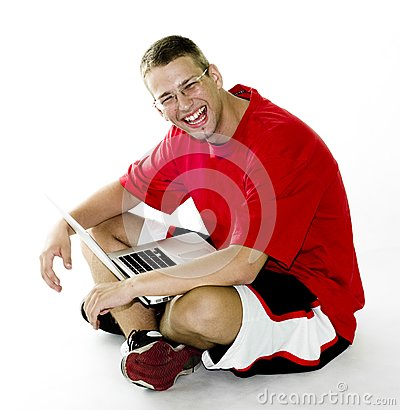 Young man sitting with laptop, laughing