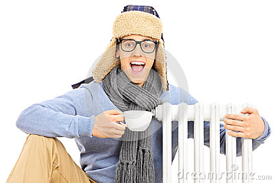 Young man sitting next to radiator holding cup of hot tea