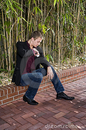 Young man sitting on patio fixing handkerchief