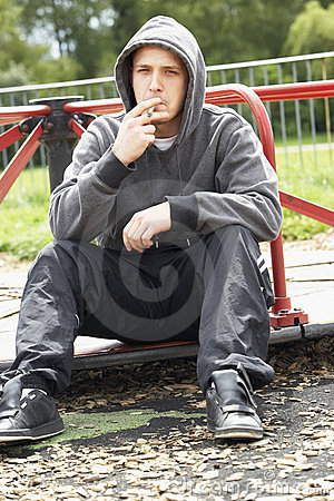 Young Man Sitting In Playground Smoking Joint