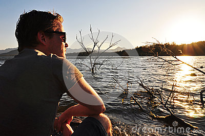 Young man sitting quietly beside lake