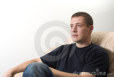 Young man sitting on sofa watching TV