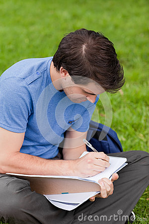 Young man sitting while writing on his notebook
